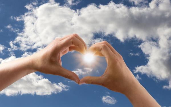 handen vormen hartje tegen blauwe lucht