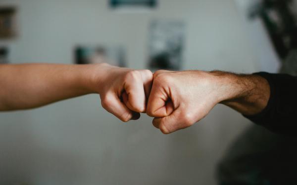 2 vuisten die vriendschappelijk tegen elkaar gedrukt worden