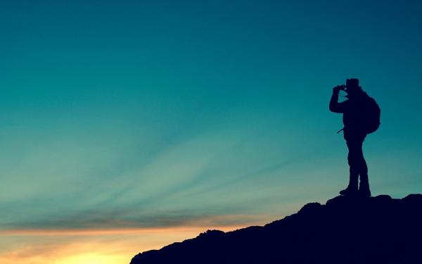 man met verrekijker kijkt uit over de heuvels