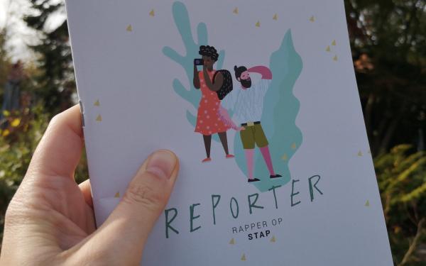 hand houdt reporterboekje Rapper op Stap vast